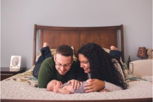 parents with baby boy on bed lifestyle newborn